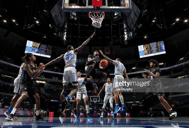 Darius Perry of the Central Florida Knights drives to the basket against Moussa Cisse and D.J. Jeffries of the Memphis Tigers during a game on...