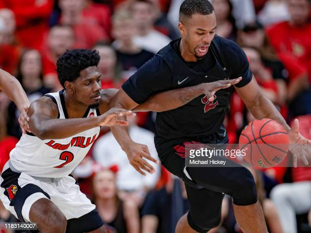 Darius Perry of the Louisville Cardinals reaches in as Jibri Blount of the North Carolina Central Eagles dribbles the ball during the first half at...