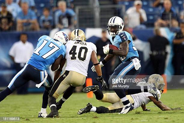 Darius Reynaud of the Tennessee Titans runs with the ball against Jonathon Amaya of the New Orleans Saints at LP Field on August 30 2012 in Nashville...