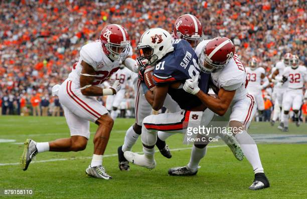 Darius Slayton of the Auburn Tigers is tackled by Minkah Fitzpatrick Hootie Jones and Anthony Averett of the Alabama Crimson Tide after catching a...