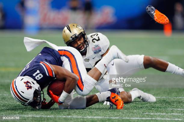 Darius Slayton of the Auburn Tigers loses his shoe as he is tackled by Tre Neal of the UCF Knights in the first half during the ChickfilA Peach Bowl...