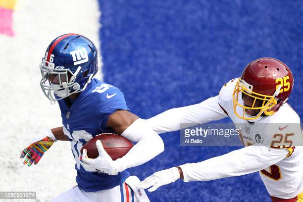 Darius Slayton of the New York Giants scores a touchdown in front of Fabian Moreau of the Washington Football Team in the first quarter of their NFL...