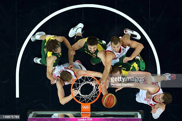 Darius Songaila of Lithuania and Andrey Kirilenko of Russia go after a rebound in the second half during the Men's Basketball quaterfinal game on Day...