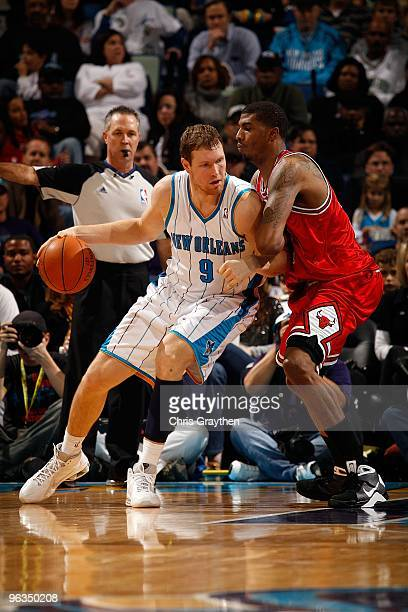 Darius Songaila of the New Orleans Hornets drives the ball around Tyrus Thomas of the Chicago Bulls at the New Orleans Arena on January 29 2010 in...