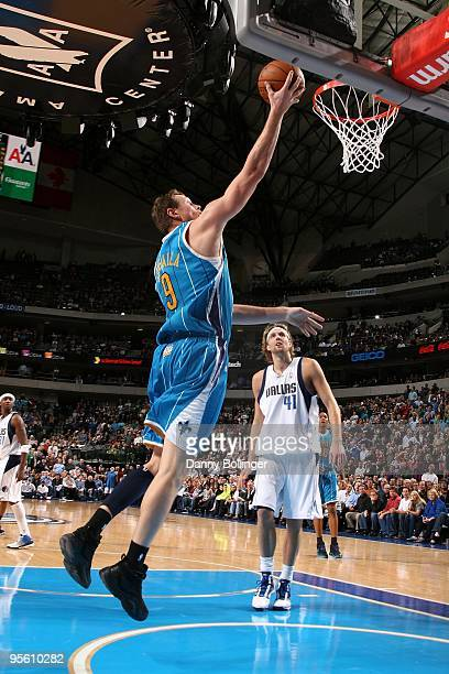 Darius Songaila of the New Orleans Hornets lays up a shot against Dirk Nowitzki of the Dallas Mavericks during the game on December 14 2009 at...