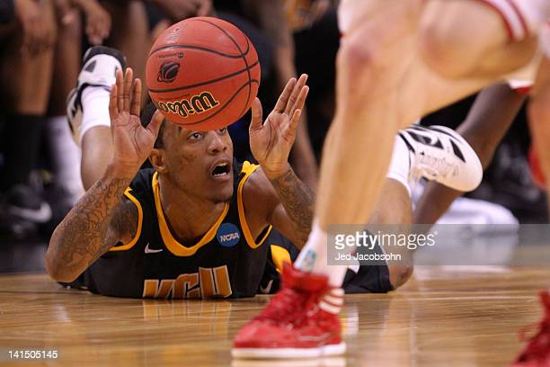 Darius Theus of the Virginia Commonwealth Rams holds the ball as he is on the ground in the first half against the Indiana Hoosiers during the third...
