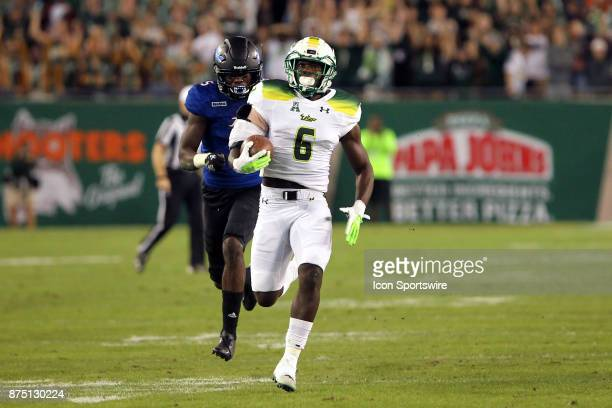 Darius Tice of South Florida takes the hand off and runs for the touchdown during the first half of the game between the Tulsa Golden Hurricane and...
