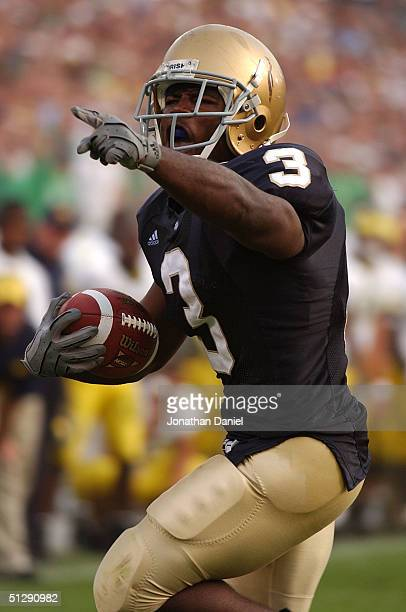 Darius Walker of Notre Dame shouts and points to fans as he runs for a touchdown against Michigan during a game on September 11, 2004 at the Notre...