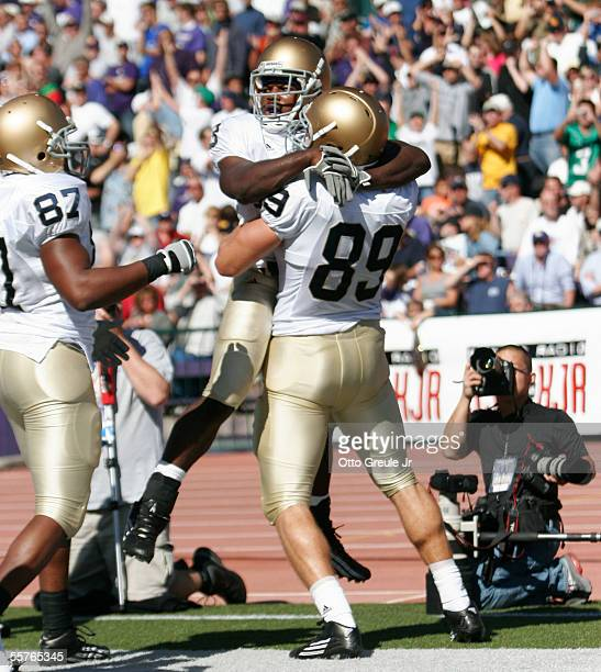 Darius Walker of the Notre Dame Fighting Irish celebrates with John Carlson and Marcus Freeman after scoring a touchdown in the first half against...