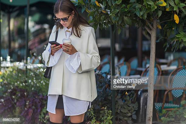Darja Barannik wearing a creme blazer while texting with her phone and drinking a coffee outside Schwedish Fashion Talents during the second day of...