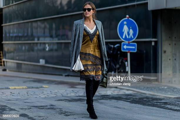 Darja Barannik wearing a grey plaid coat golden dress and overknee boots outside Lala Berlin during the first day of the Copenhagen Fashion Week...