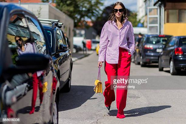 Darja Barannik wearing a pink button shirt from Ganni red wide pant and yellow Gucci bag outside Ganni during the second day of the Copenhagen...