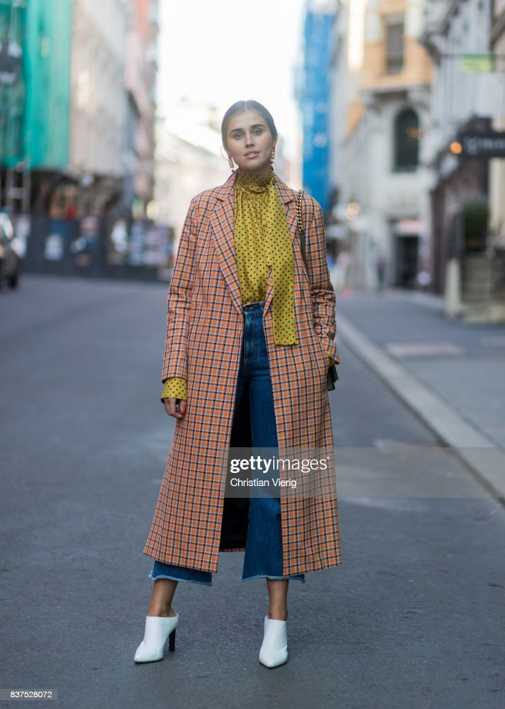 Darja Barannik wearing a plaid coat, yellow button shirt, white boots, cropped denim jeans outside Line of Oslo on August 22, 2017 in Oslo, Norway.