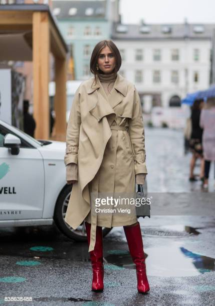 Darja Barannik wearing a trench coat red boots green bag outside Bik Bok Runway Award on August 24 2017 in Oslo Norway