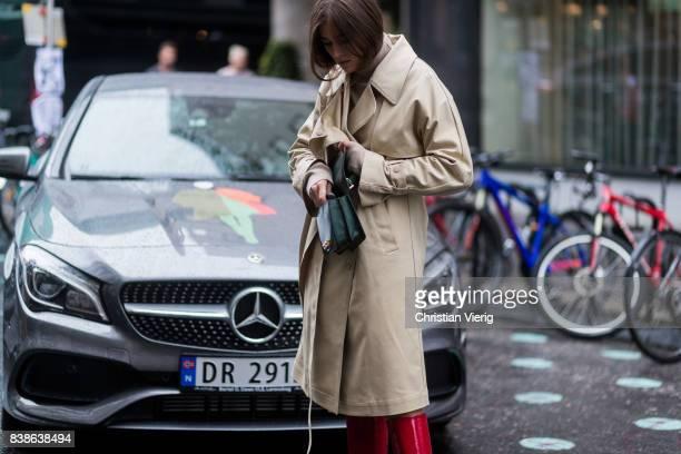 Darja Barannik wearing a trench coat red boots green bag outside Bik Bok Runway Award on August 24 2017 in Oslo Norway