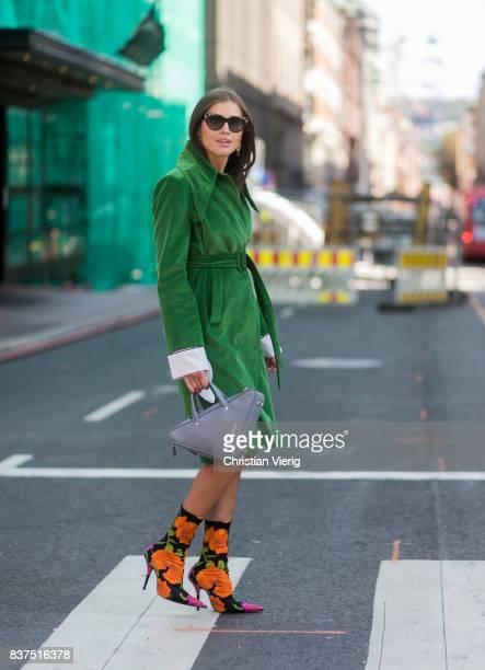 Darja Barannik wearing Balenciaga bag green coat Balenciaga sock boots outside Moods of Norway on August 22 2017 in Oslo Norway