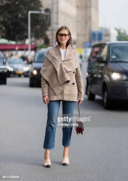 Darja Barannik wearing beige checked jacket Chanel shoes red Gucci bag denim jeans outside House of Dagmar on August 31 2017 in Stockholm Sweden