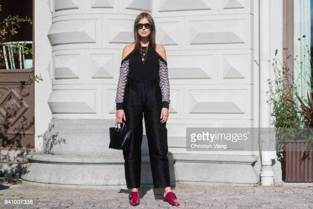 Darja Barannik wearing off shoulder top, black pants, red slippers outside Stylein on August 30, 2017 in Stockholm, Sweden.