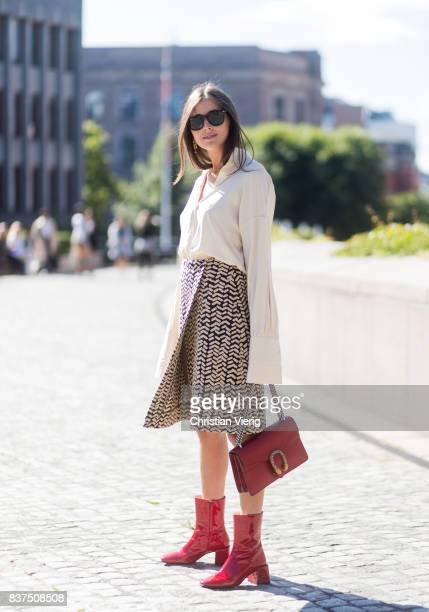 Darja Barannik wearing white blouse skirt red Gucci bag and red boots outside IBEN on August 22 2017 in Oslo Norway