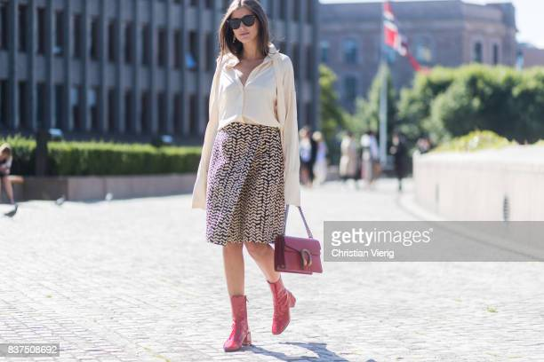 Darja Barannik wearing white blouse, skirt, red Gucci bag and red boots outside IBEN on August 22, 2017 in Oslo, Norway.
