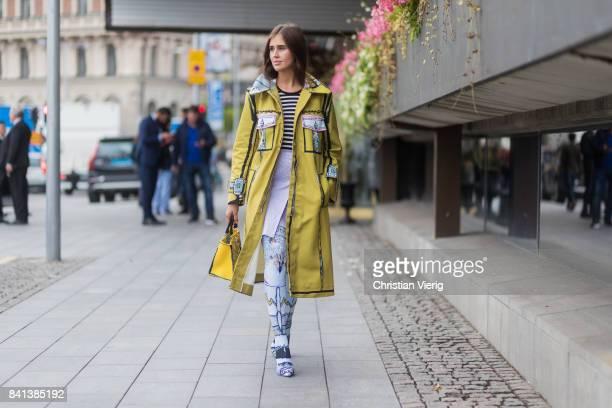 Darja Barannik wearing yellow Edda coat bag and sock boots outside Jennifer Bloom on August 31 2017 in Stockholm Sweden