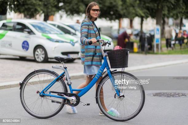 Darja Barannik with her bike wearing a denim skirt red Gucci skirt striped blazer outside Baum Und Pferdgarten on August 10 2017 in Copenhagen Denmark