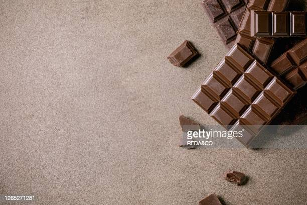 Dark and milk chocolate bar whole and chopped over brown texture background. Flat lay, space.