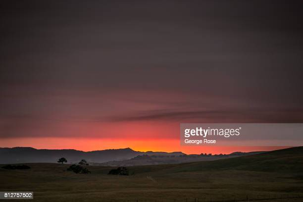 Dark billowing late afternoon smoke caused by the Whittier Fire burns in the coastal mountains creating an eerie sunset on July 8 near Santa Ynez...