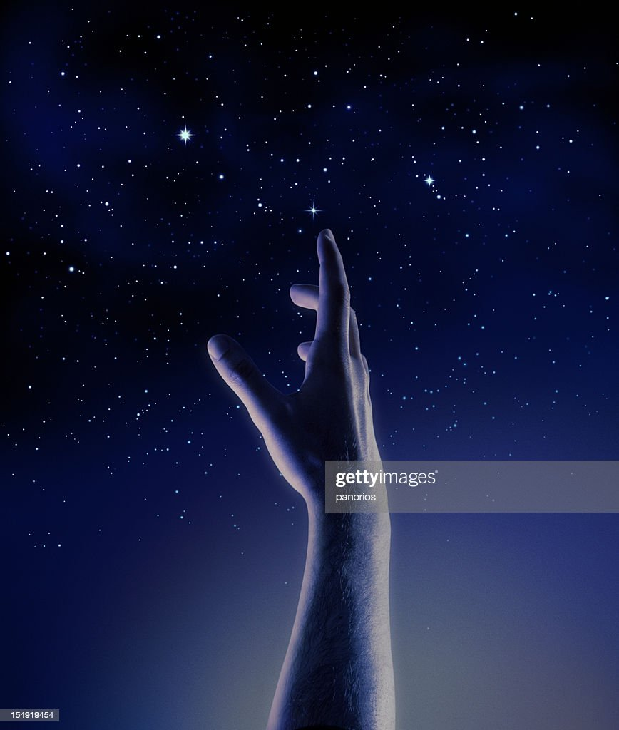Dark blue and black Graphic of a hand reaching for stars : Stock Photo