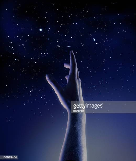 Dark blue and black Graphic of a hand reaching for stars