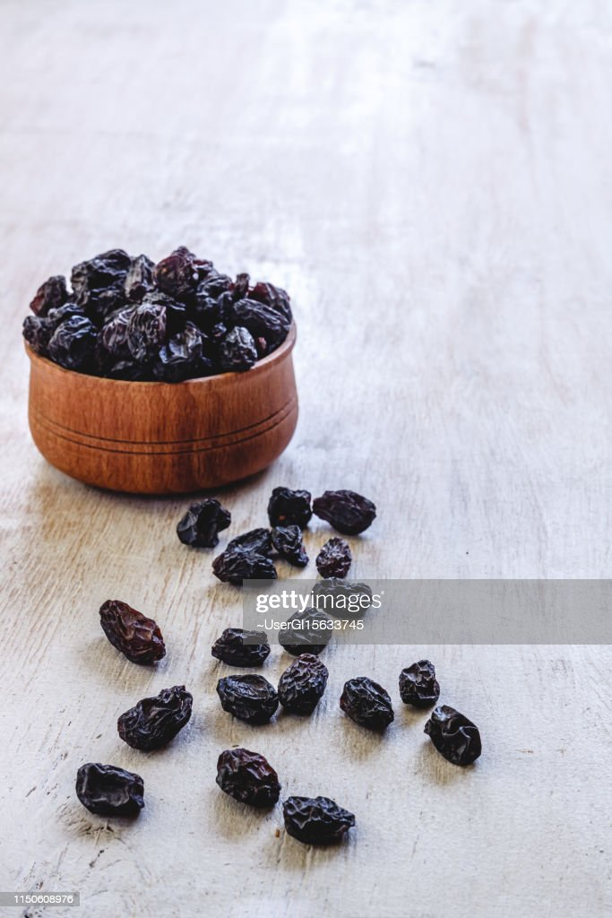Dark blue raisins in a wooden bowl on a bright white background. Close-up. Insulated. : Stock Photo