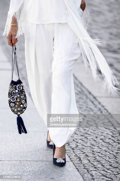 Dark blue sandals with strass stones and a dark blue bag with strass details by Lipsy Londonas a detail of influencer Maria Gieseke during a street...