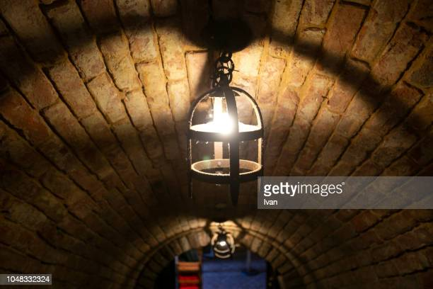 dark cellar with small old kerosene lamp - dungeon stock photos and pictures