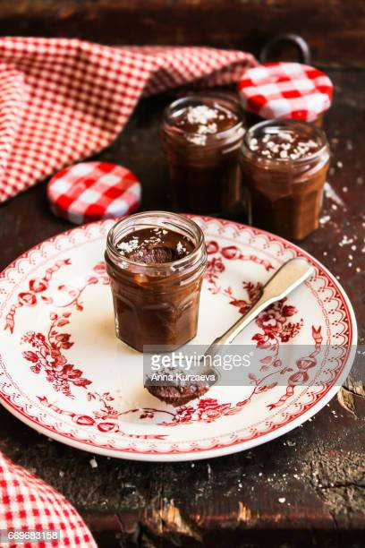 dark chocolate mousse with freshly shredded coconut in jars on a wooden table, selective focus - chocolate mousse stock pictures, royalty-free photos & images