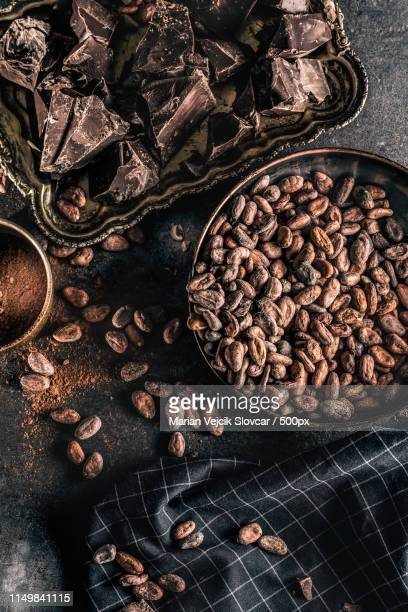 Dark Chokolate Cocoa Beans And Powder On Concrete Table