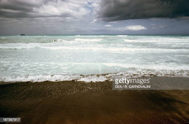 Dark clouds and storm approaching to the white beach of Rosignano Solvay Tuscany region Italy