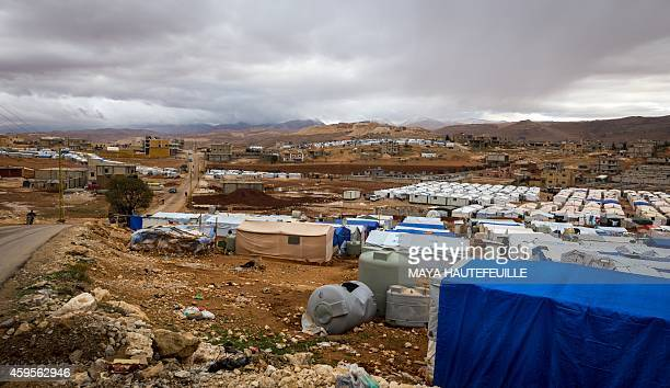 Dark clouds are seen over the AlNihaya Syrian refugee camp in the eastern Lebanese town of Arsal on October 23 2014 With more than 11 million Syrian...