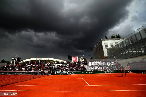 Dark clouds begin to cover the court during the men's singles first round match between Cameron Norrie of Great Britain and Elliot Benchetrit of...