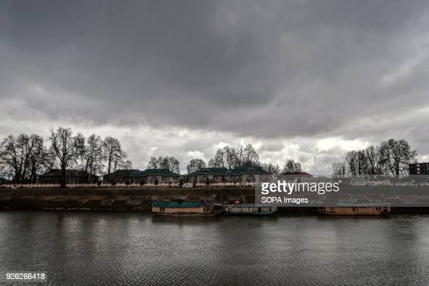 Dark clouds hover over the river Jehlum on a partly cloudy day in Srinagar Indian administered Kashmir Ahead of prediction of rain and snow from...