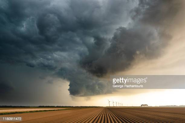 dark clouds over an agricultural field - cielo minaccioso foto e immagini stock
