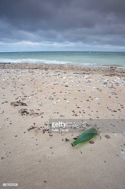dark clouds over green bottle on baltic beach, estonia - bottle green stock pictures, royalty-free photos & images