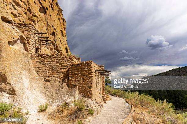 dark clouds over pueblo ruins at bandelier national monument - pueblo built structure stock pictures, royalty-free photos & images