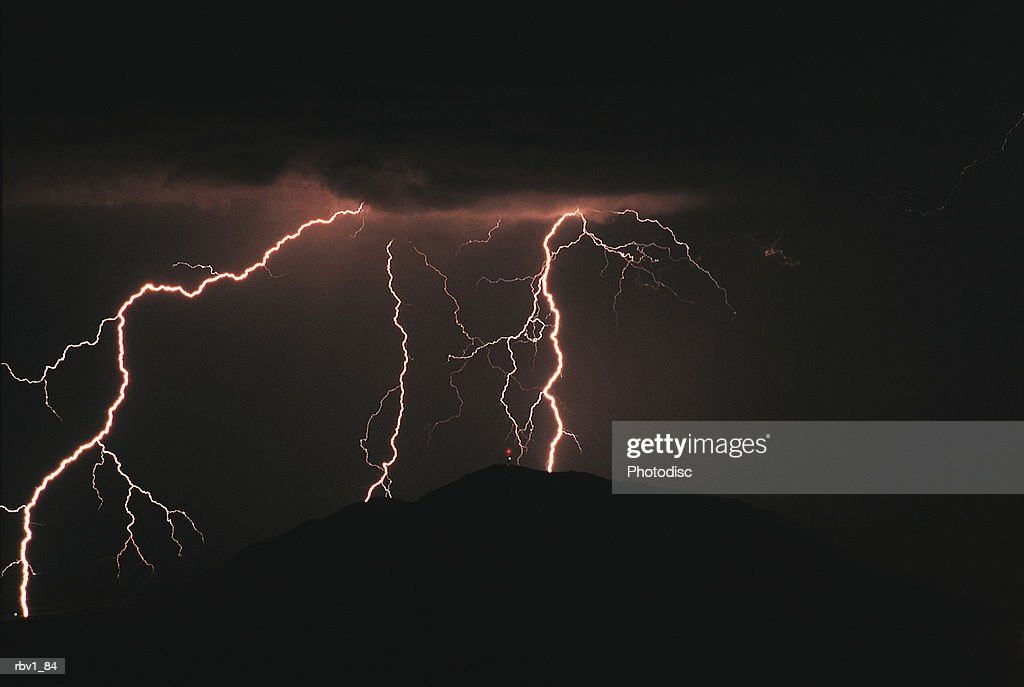 dark clouds release bright pink branching lightning bolts to the ground blow : Foto de stock