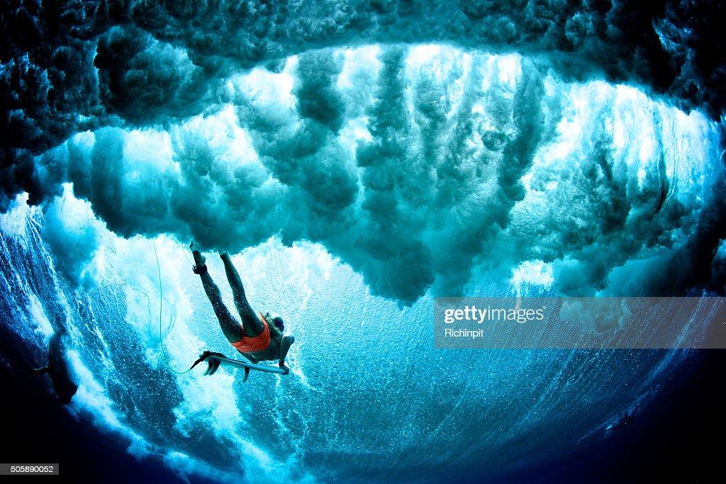 Dark cloudy duck dive surfer : Stock Photo