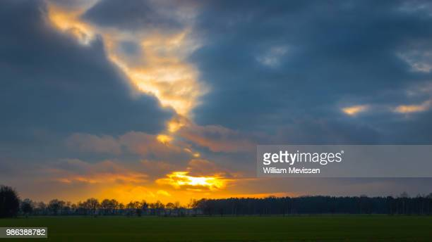 dark cloudy sunset - william mevissen stock pictures, royalty-free photos & images
