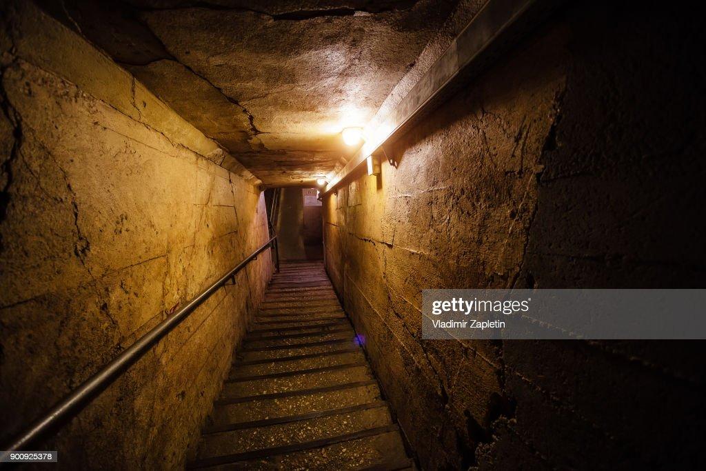Dark corridor of old underground Soviet bunker under military artillery fortification : Stock Photo