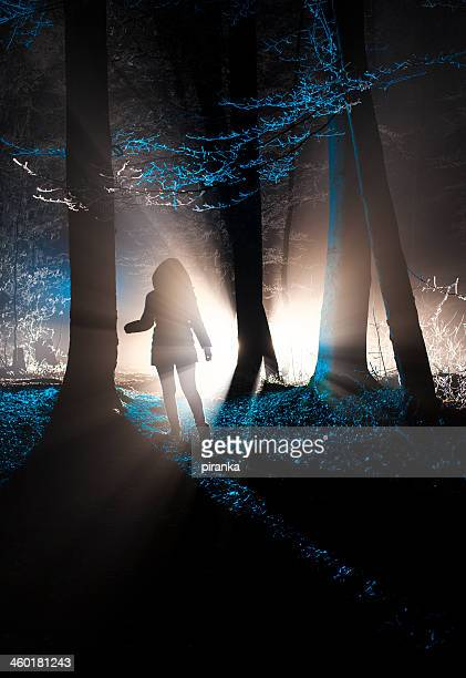 Dark figure in a misty winter forest at night
