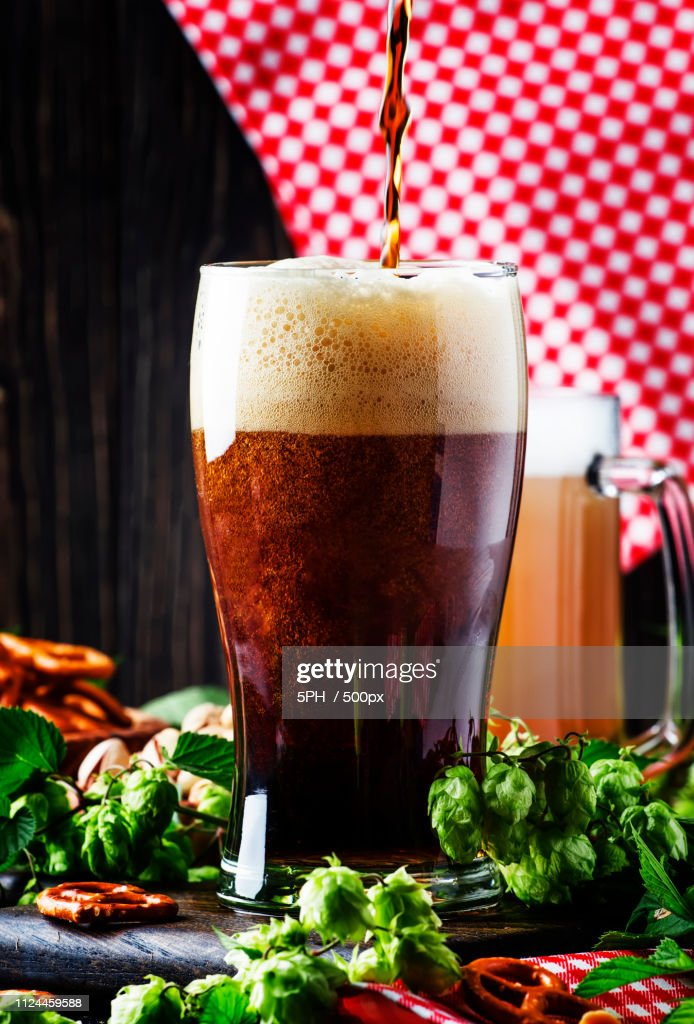 Dark German Beer Is Poured Into A Glass Fresh Green Hops And