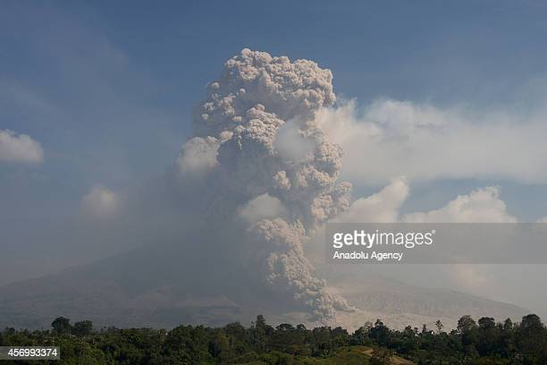 A dark giant ash clouds rises from the crater of Mount Sinabung volcano during an eruption following an earlier eruption on October 5 2014 at Siroga...