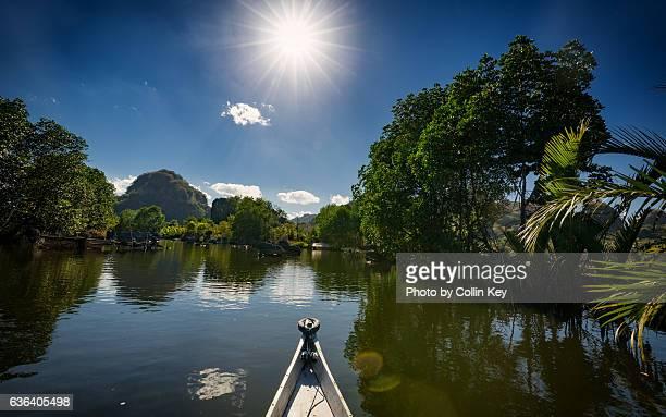 dark green tropical river below a hot glistening sun. - collin key stock-fotos und bilder